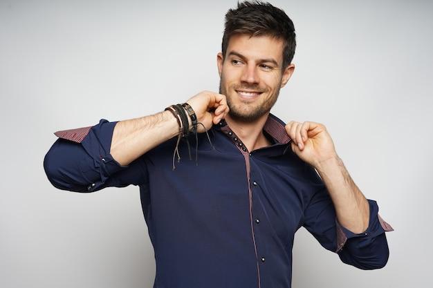 Closeup portrait of smiling male tenant avec confiance son collier et isolé sur mur blanc