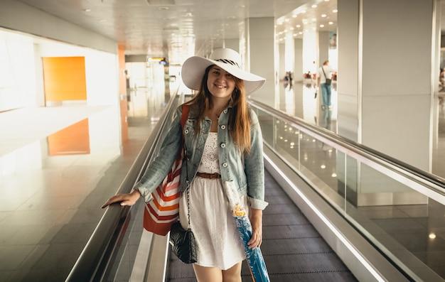 Closeup portrait of smiling woman wearing hat à l'aéroport à l'escalator