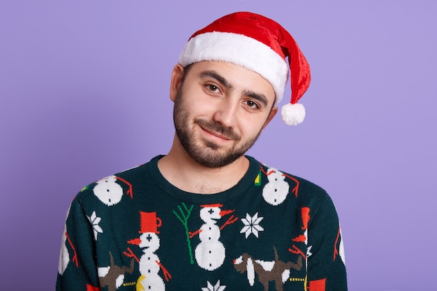Closeup portrait of sweet good looking young man with beard wearing new year pull with snowmen and red santa claus hat
