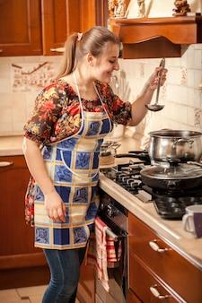 Closeup portrait of woman dégustation de soupe avec cuillère de cuisine