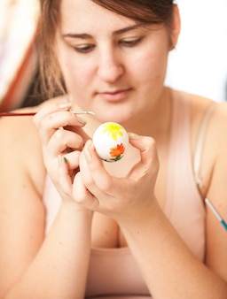 Closeup portrait of young brunette woman painting white easter egg