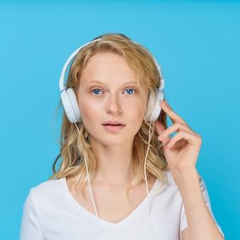 Closeup portrait of young woman écoute de la musique via des écouteurs sur ton bleu vif de couleur
