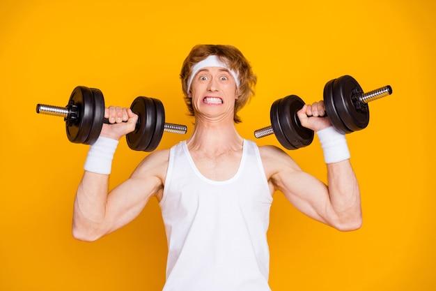 Closeup portrait de sportif guy auto motivé soulevant des haltères lourdes