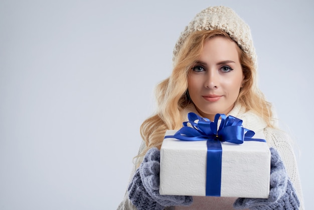 Closeup portrait de stupéfiante femme tenant cadeau du nouvel an