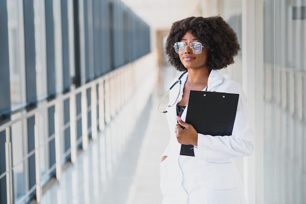 Closeup portrait de tête de professionnel de la santé féminin confiant sympathique et souriant avec blouse de laboratoire, bras croisés tenant des lunettes. fond de clinique hôpital isolé. temps pour une visite au bureau