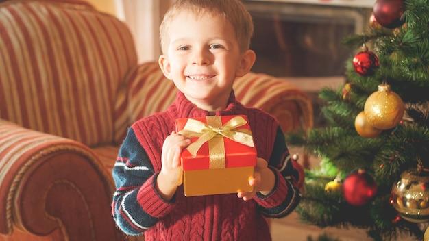 Closeup portrait tonique d'un petit garçon souriant heureux tenant une boîte avec un cadeau ou un cadeau de noël et regardant à huis clos