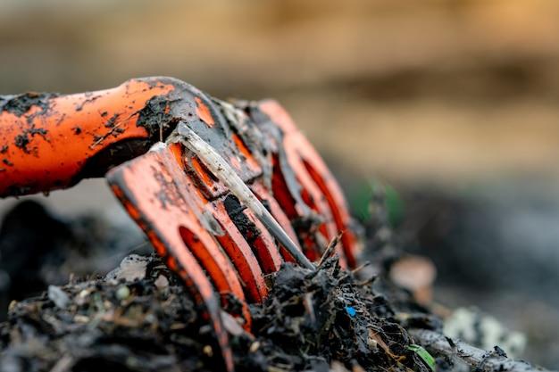 Closeup râteau orange sur tas de déchets plastiques sales sur fond flou. concept de pollution environnementale de plage nettoyez les déchets sur la plage. déchets océaniques. côte polluée.