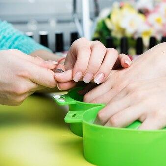 Closeup shot d'une femme dans un salon de manucure recevant une manucure