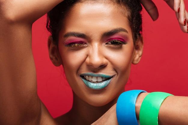 Closeup, sourire, femme américaine africaine, à, mode, maquillage, regarder appareil-photo, projection, mains, à, bracelets, sur, mur rouge