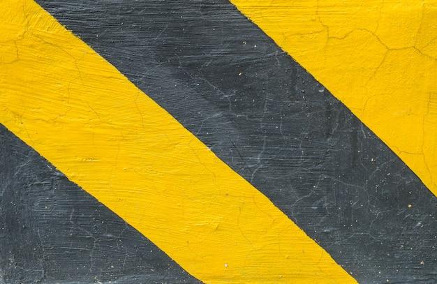 Closeup surface de la vieille texture de sol en ciment peint jaune et noir