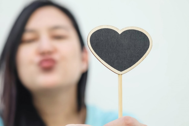 Closeup tableau en bois noir en forme de coeur avec floue envoyer un visage de baiser de fond de femme