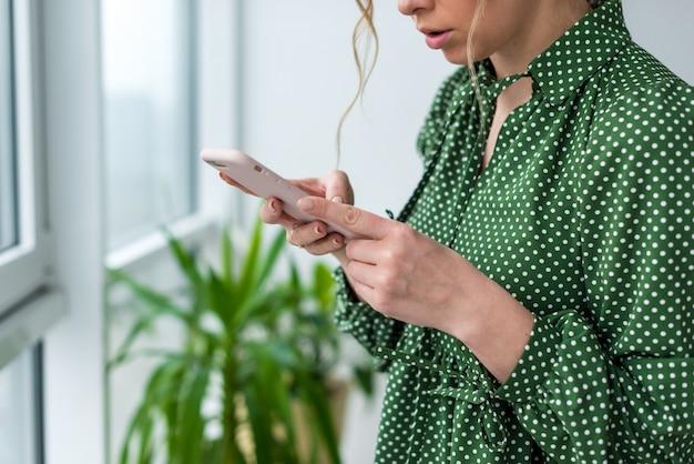 Closeup un téléphone portable dans les mains féminines. femme regardant l'écran - image