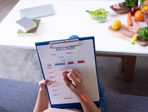 Closeup the diet plan form a été écrit à la main, pour enregistrer des données relatives à la réduction de poids et à la lumière floue.
