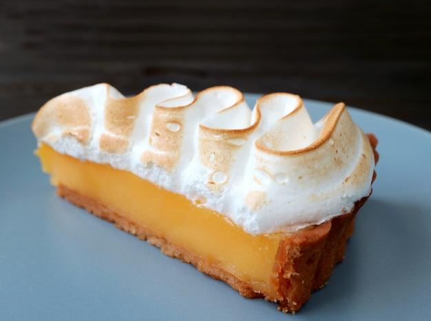 Closeup, une tranche de tarte meringuée au citron sur une assiette bleue