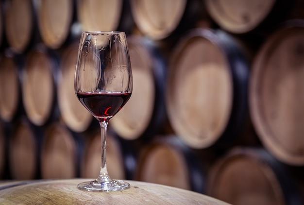 Closeup verre de vin rouge sur fût de chêne de vin en bois empilés en rangées droites dans l'ordre, ancienne cave de cave, cave voûtée. dégustation professionnelle, winelover, sommelier travel