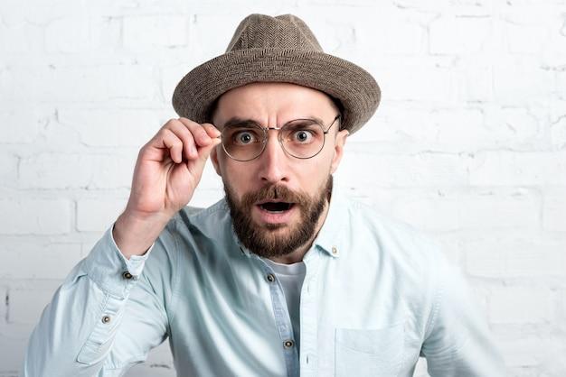 Closeup visage portrait d'homme barbu dans le chapeau et les lunettes à la recherche. surprise d'émotion, indignation