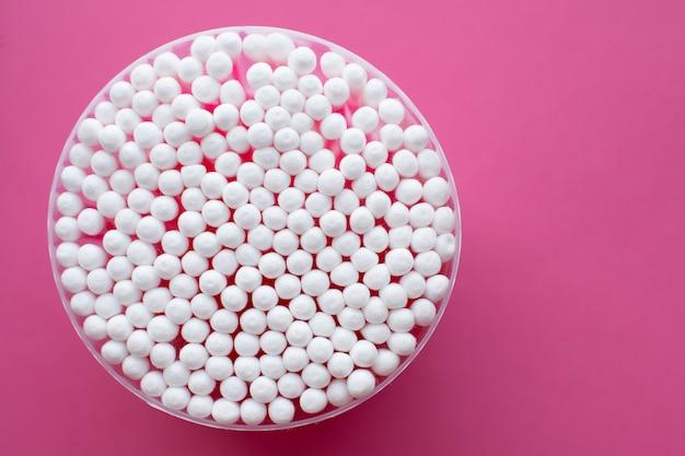 Closeup vue d'en haut sur un sac rond de coton tige sur fond rose
