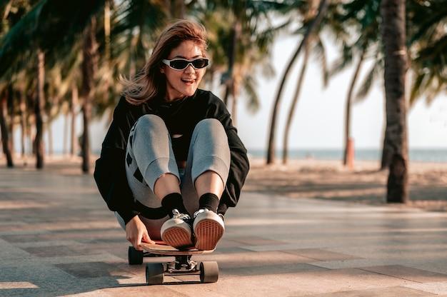 Closeuples femmes asiatiques surfent du skate ou du skateboard à l'extérieur par une belle journée d'été