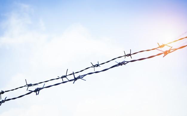 La clôture de barbelés silhouette, en fer, épine et rouille utilisée depuis longtemps