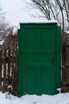 Clôture en bois avec belle porte d'entrée en bois vert classique avec poignée