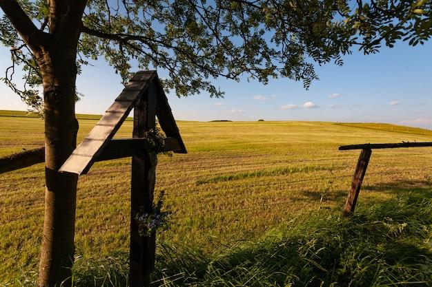 Clôture en bois sur un champ herbeux sec sous un ciel bleu dans l'eifel, allemagne