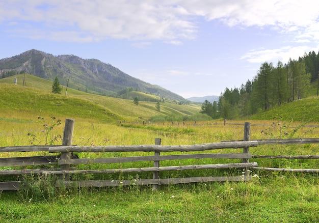 Une clôture en bois sur un champ vert sur fond de montagnes sous un ciel bleu nuageux sibérie