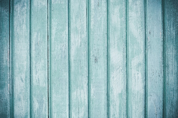 Clôture en bois clair avec peinture écaillée. planches de bois décrépites minables. lamelles en bois. surface des planches peintes en bleu brut. fond d'écran abstrait. fond vintage. élément de texture.