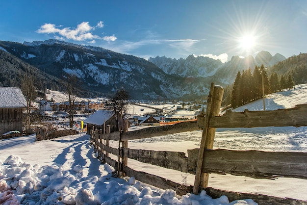 Clôture en bois dans un champ couvert de neige. vieille clôture grise dans la neige. journée ensoleillée et vieille clôture