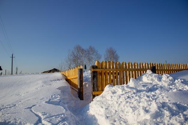 Clôture en bois dans la neige. fond de neige.