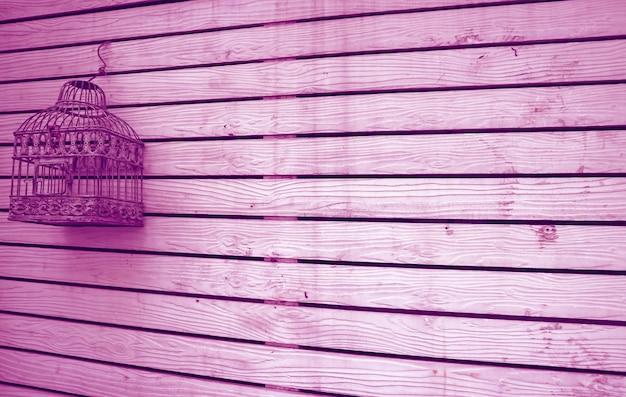 Clôture en bois grunge de couleur violet orchidée avec une cage à oiseaux vide