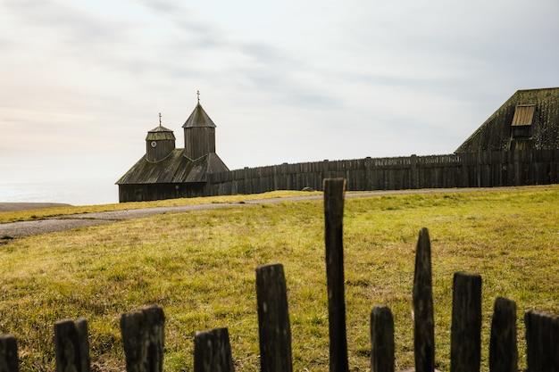 Clôture en bois marron sur champ d'herbe verte pendant la journée
