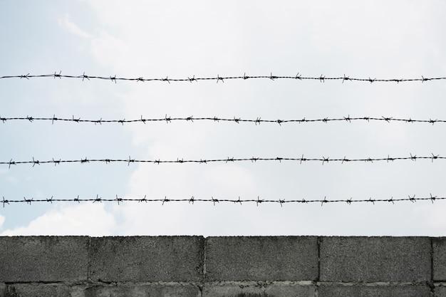Clôture de briques de ciment de fil de fer barbelé et ciel bleu