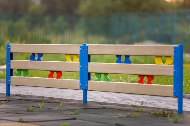 Clôture décorative basse multicolores en bois ou en plastique à l'extérieur par une journée d'été ensoleillée.