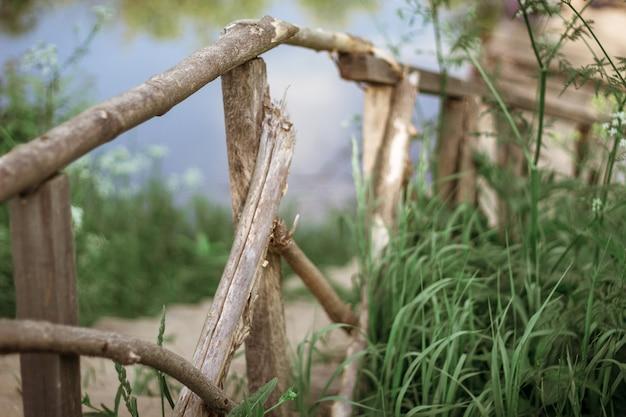 Une clôture d'échelle en bois descend jusqu'à un pont sur la rivière parmi les hautes herbes vertes. le concept de paix et de tranquillité. horizontal. mise au point sélective.