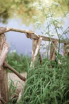 Une clôture d'échelle en bois descend jusqu'à un pont sur la rivière parmi les hautes herbes vertes. le concept de paix et de tranquillité. verticale. mise au point sélective.