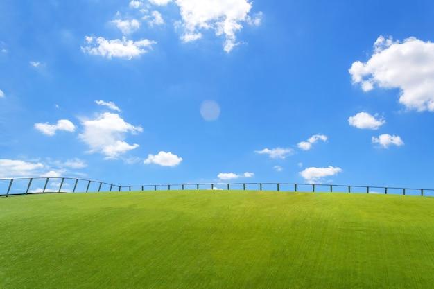 Clôture de fer sur l'herbe verte et le ciel bleu wallpaper