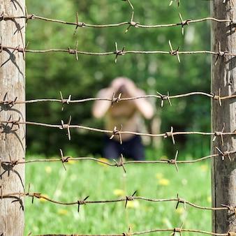 Clôture en fil de fer barbelé au premier plan et un homme déprimé à l'arrière-plan