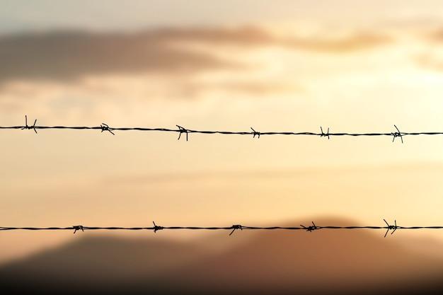 Clôture en fil de fer barbelé avec ciel crépusculaire pour se sentir silencieux et solitaire et vouloir la liberté