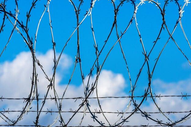 Clôture avec fil de fer barbelé contre le ciel bleu avec des nuages