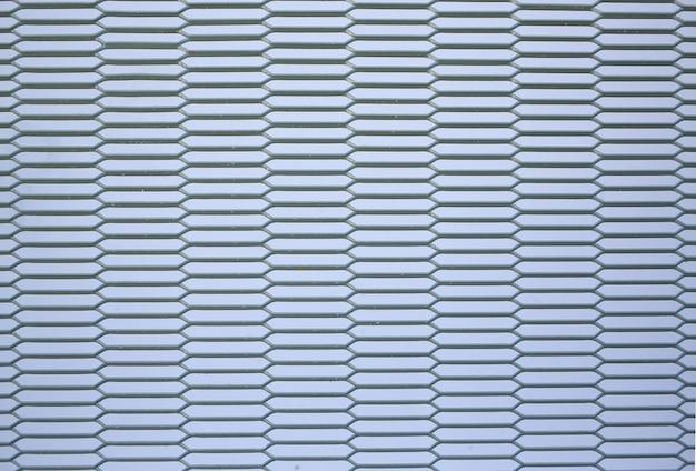 Clôture de grille en métal gris sur fond de mur blanc.