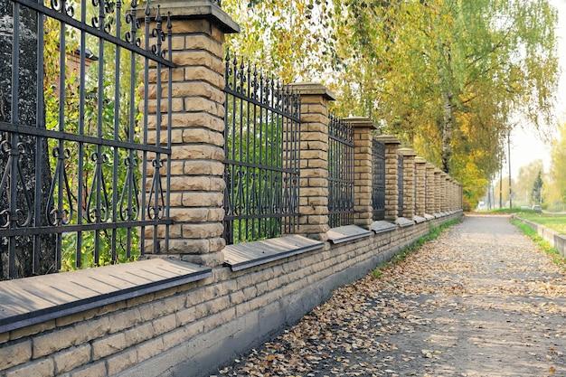 Clôture en pierre avec perspective linéaire de treillis usés dans des tons d'automne