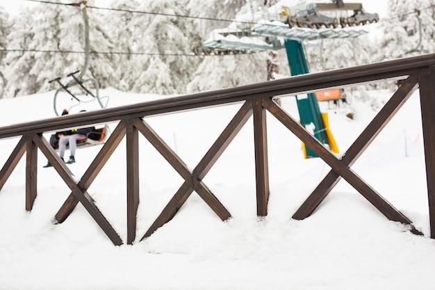 Clôture et piste de ski avec remontée mécanique en arrière-plan