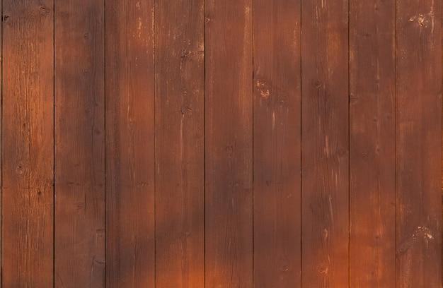Clôture de planche verticale en bois marron avec éblouissement du soleil.