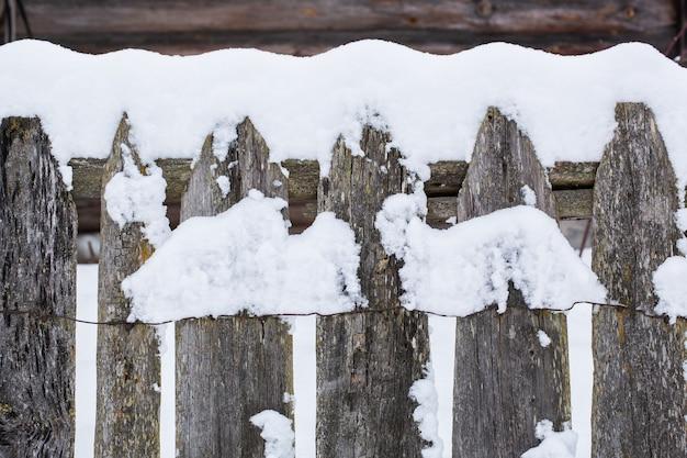 Clôture rurale en bois brun recouverte de neige
