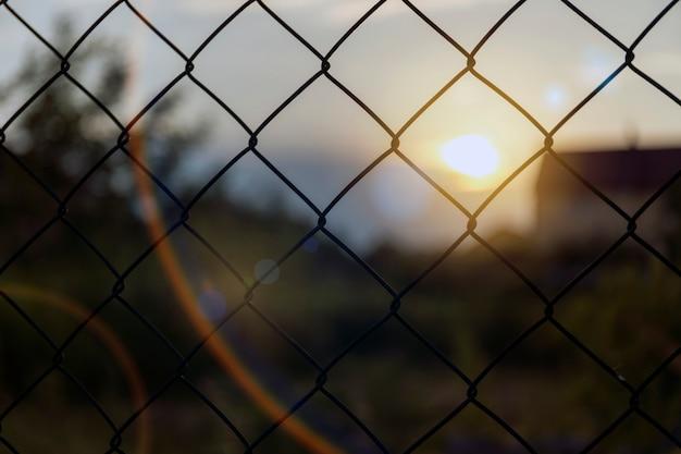 Clôture sécurisée au coucher du soleil avec bokeh.