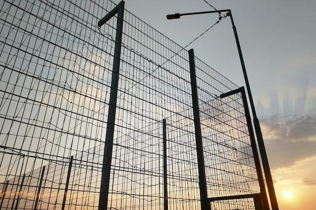 Clôture en treillis métallique dans une zone réglementée sur fond de ciel bleu.