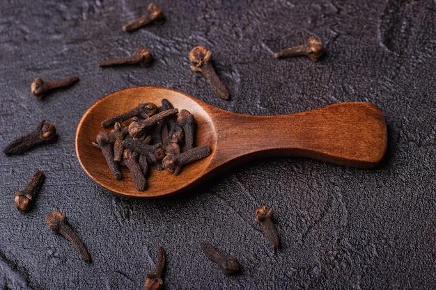 Clou de girofle dans une cuillère en bois contre un béton foncé