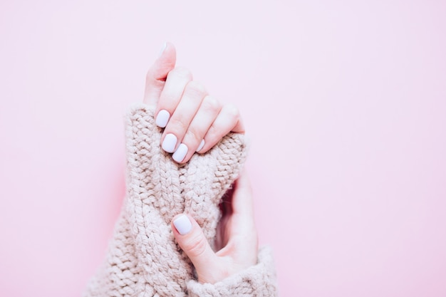 Clou tendance élégante jeune femme mains manucure bleu clair sur fond rose. manucure féminine à la mode élégante. vue de dessus. mains de belle jeune femme sur fond rose. copiez l'espace libre.