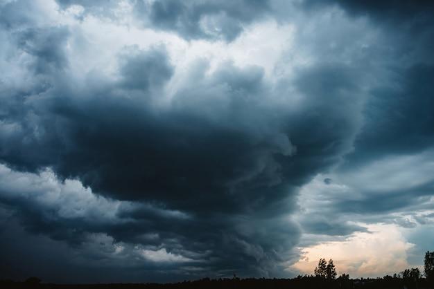 Cloudscape dramatique. lumière ensoleillée à travers de gros nuages orageux sombres avant la pluie. couvert pluvieux mauvais temps. avertissement de tempête. fond bleu naturel de cumulonimbus. la lumière du soleil dans le ciel nuageux orageux.
