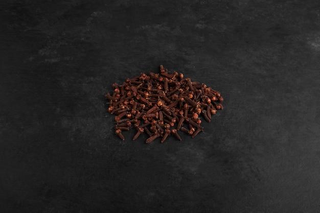 Clous de girofle secs isolés sur une surface noire.